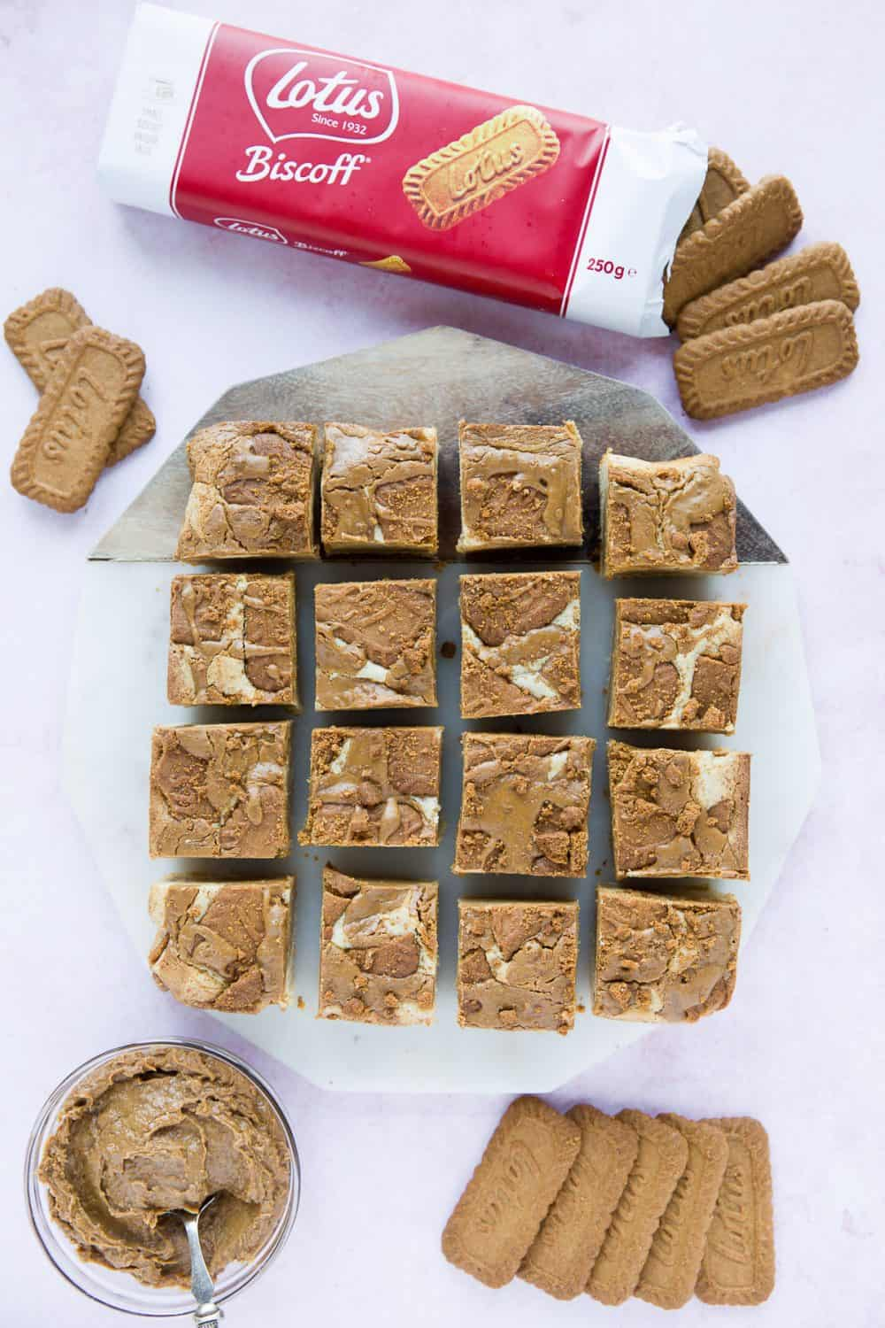 Lotus Biscoff and White Chocolate Blondies cut into 12 equal squares surrounded by an open packet of Lotus biscuits and some biscoff spread in a bowl.