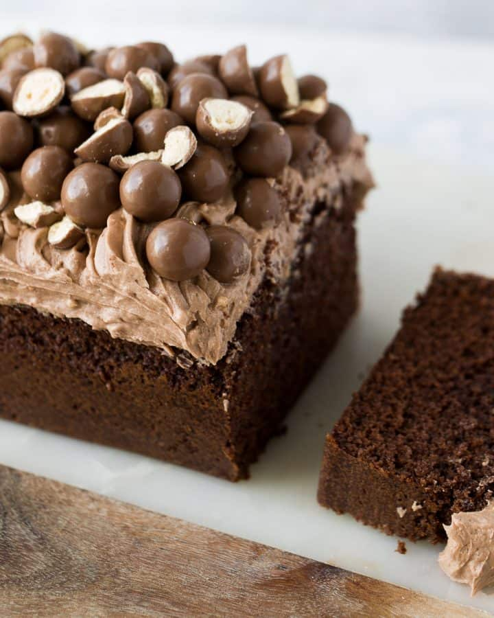 A Malteser loaf cake that has a slice cut out.