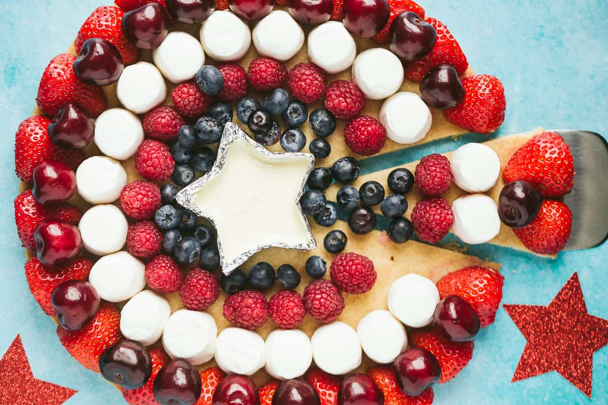 A fruit pizza with a slice cut out.
