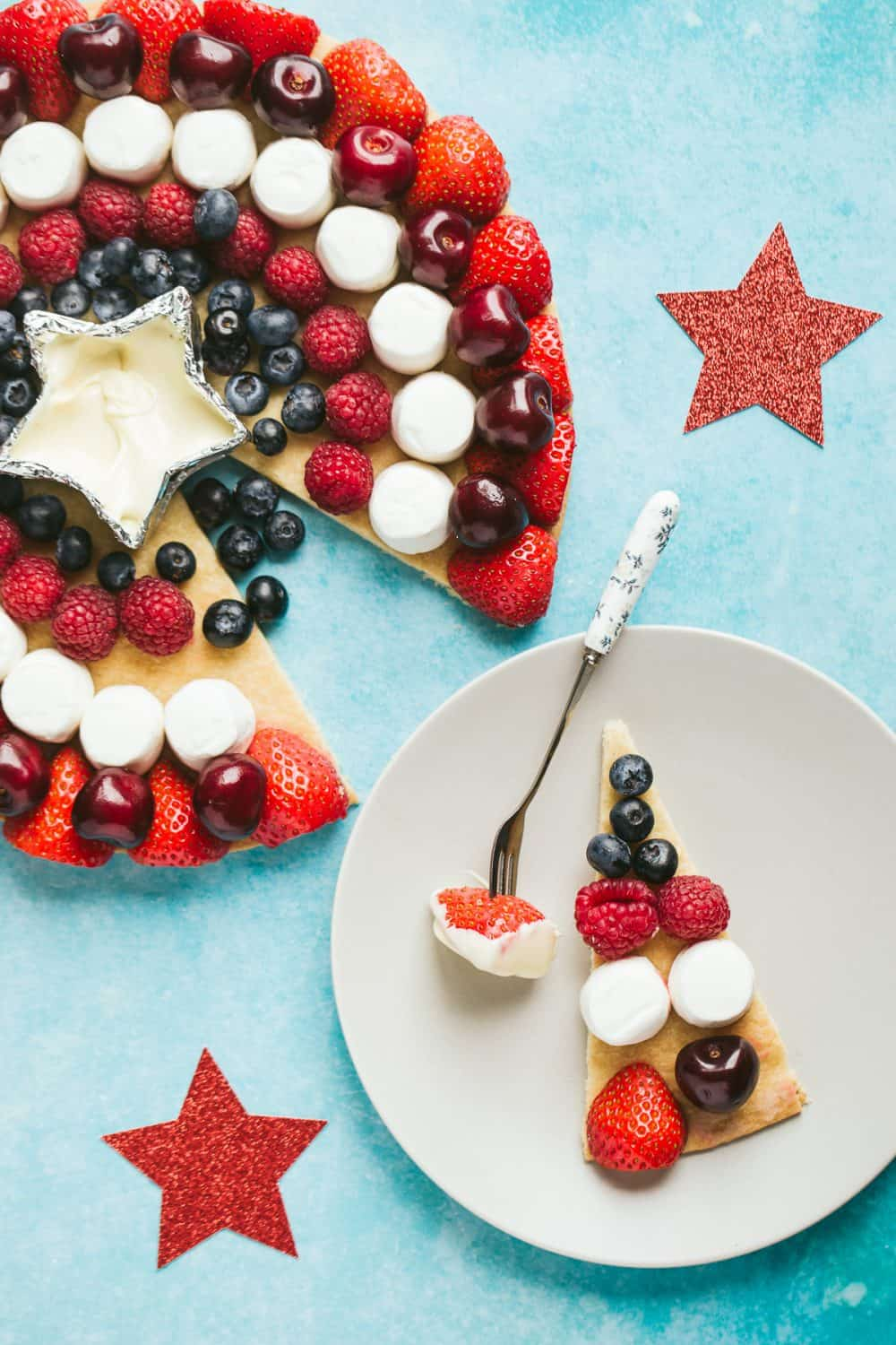 A fruit platter in the shape of a Captain America Shield with a slice cut out on a small plate.