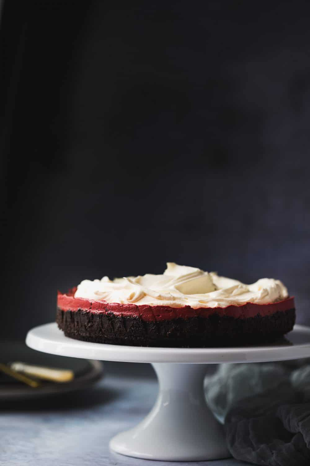 A no bake red velvet cheesecake on a white cake stand.