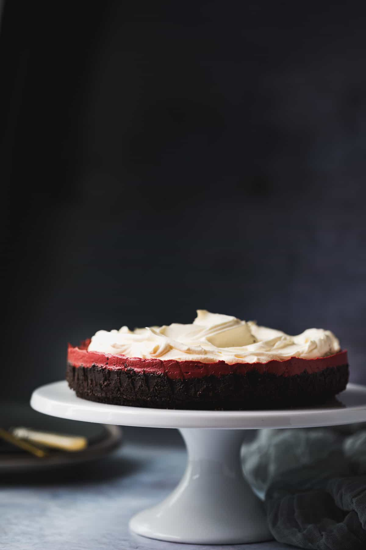 A red velvet cheesecake on a white cake stand.