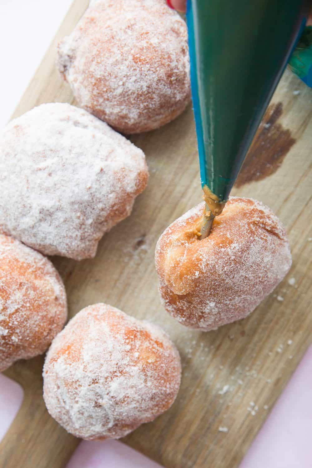 A piping bag fitted with a doughnut nozzle, filling a freshly made doughnut.