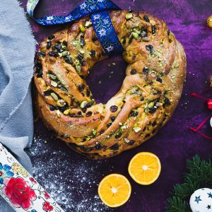 A Stollen wreath surrounded by christmas decorations, fresh oranges and a decorative rolling pin on a dark purple background.