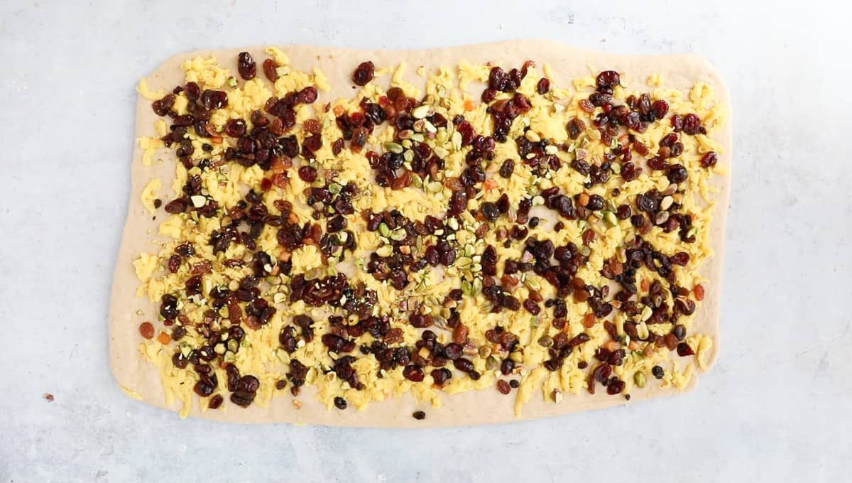 Dough scattered with marzipan, cranberries, dried fruit and pistachio nuts.