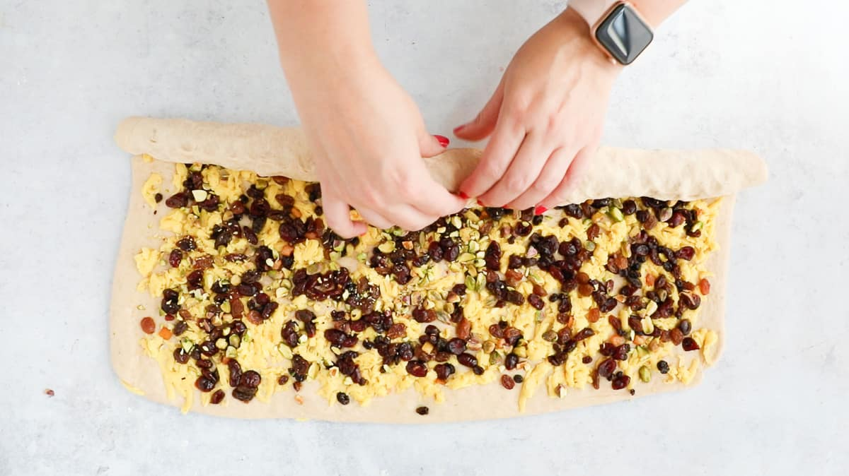 Image demonstrating how to roll up dough for a stollen babka wreath.