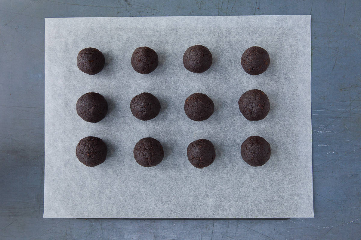 12 chocolate cake pops on a baking tray lined with baking paper.