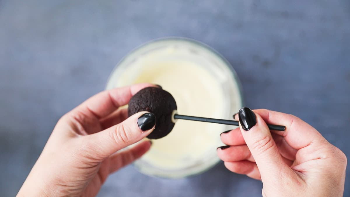 Pushing a cake pop stick into the middle of a chocolate cake ball.