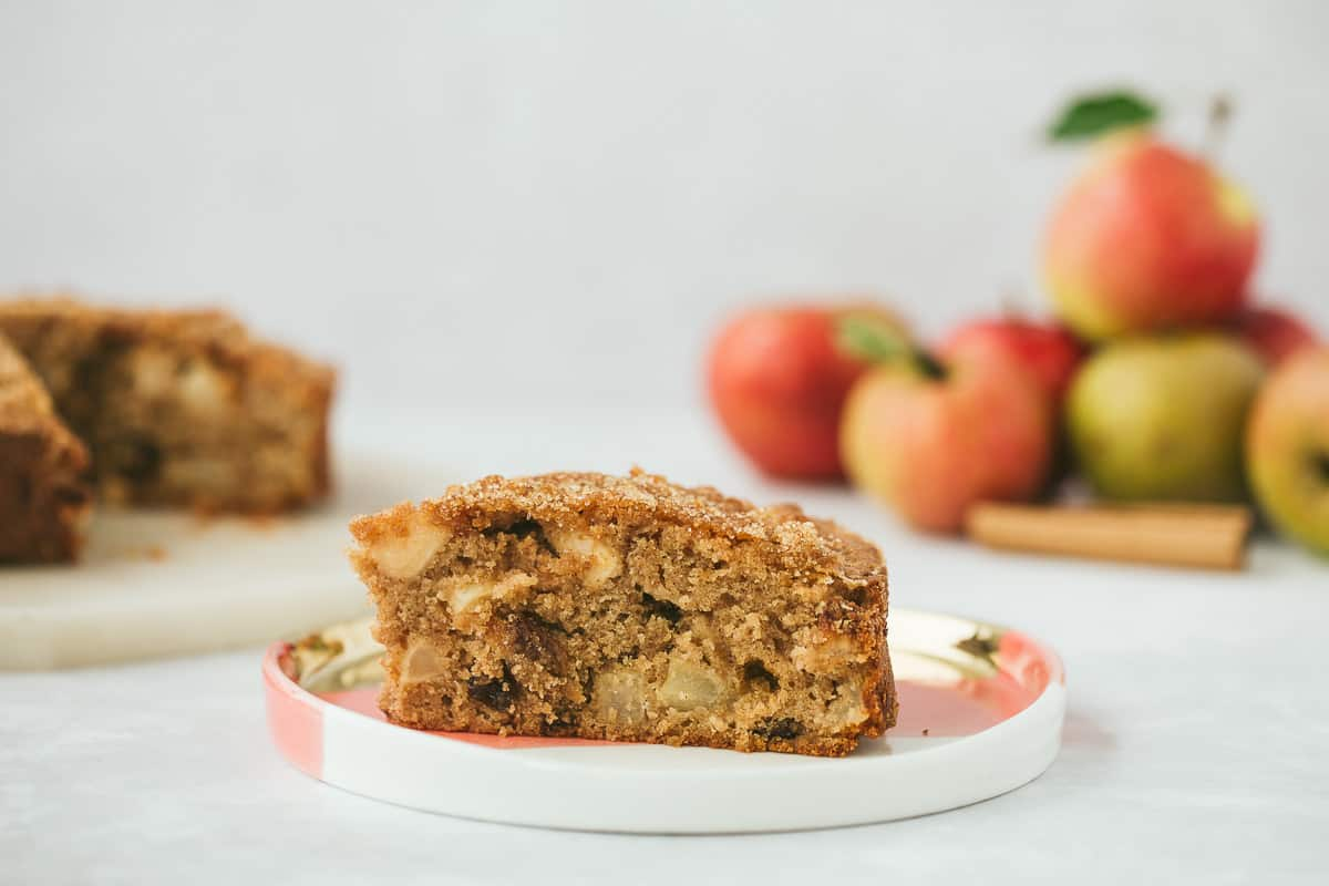a slice of apple and sultana cake on a pink, white and gold plate.
