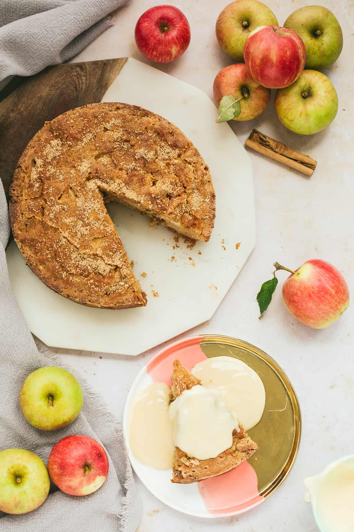 A round Dorset Apple Cake with a slice cut out. The slice is on a plate next to the cake and has custard poured over the top of it.