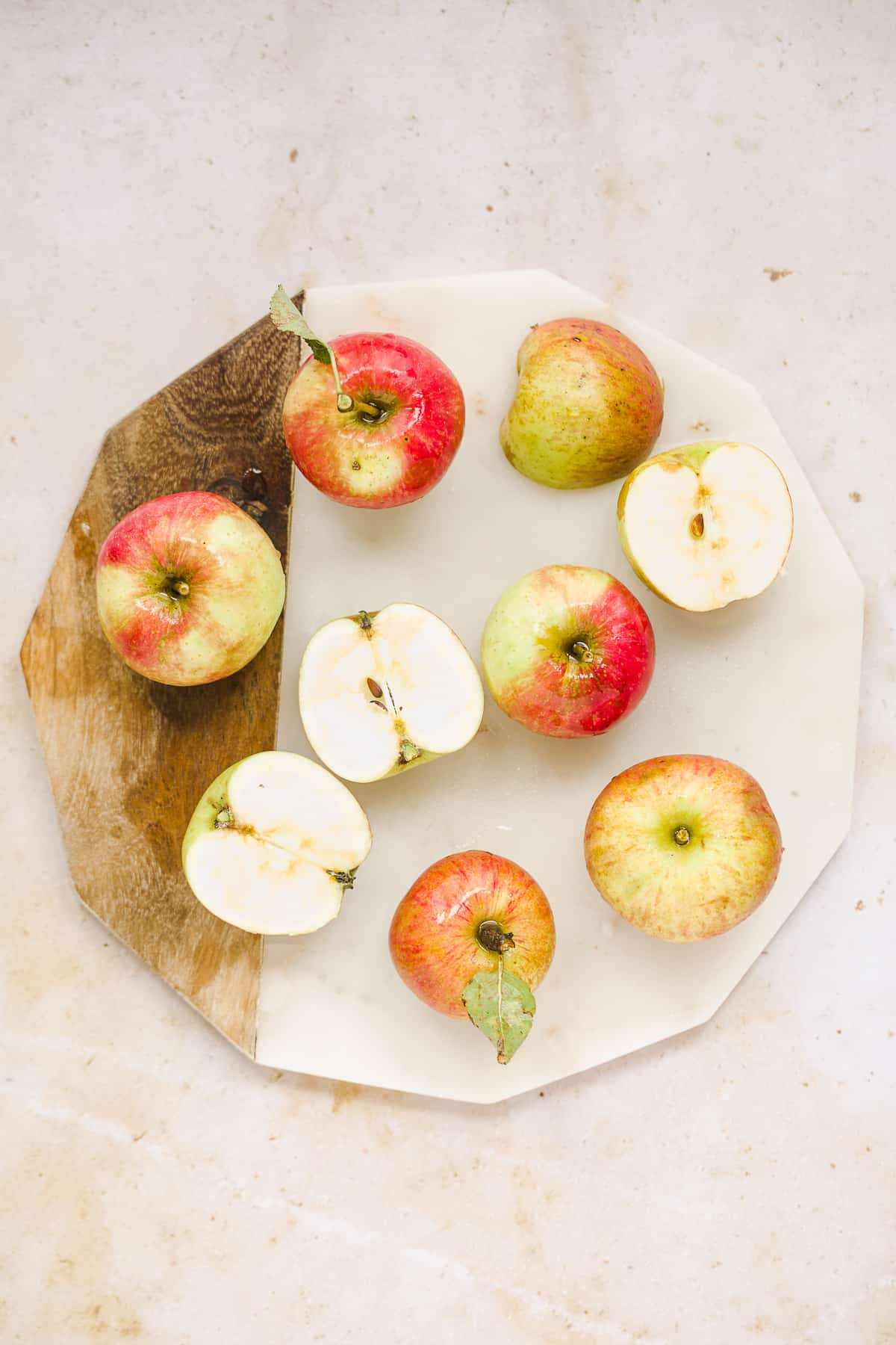Freshly picked apples on a marble chopping board.