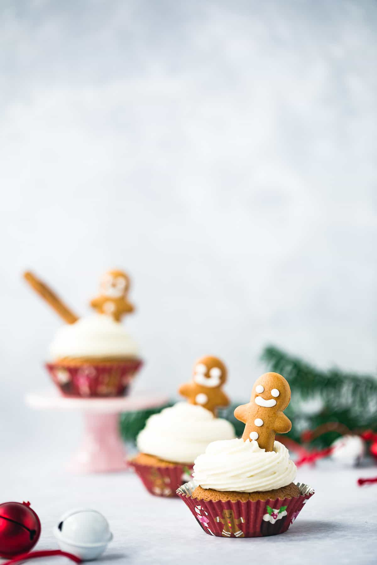 3 christmassy cupcakes surrounded by christmas baubles.