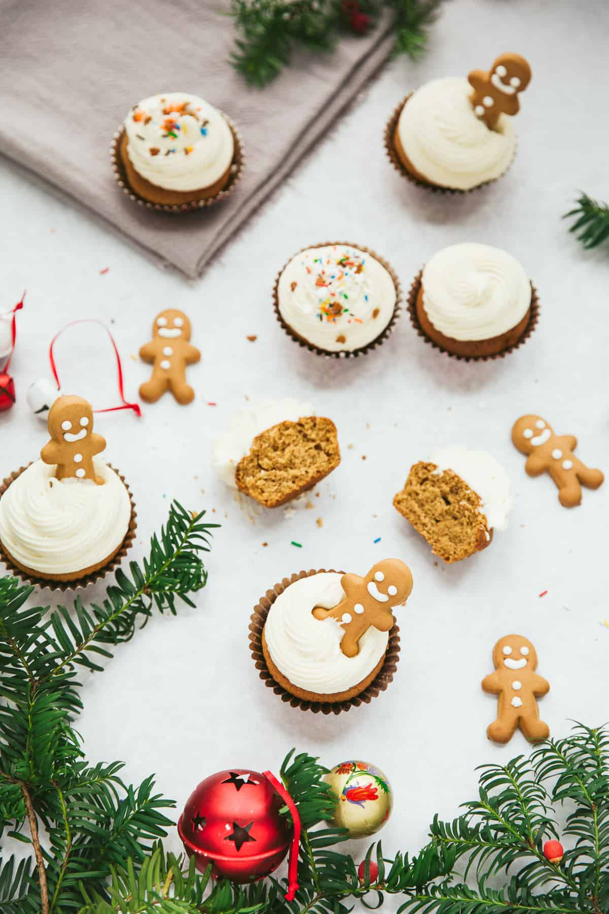 Overhead shot of cupcakes covered in a white coloured frosting surrounded by gingerbread men.