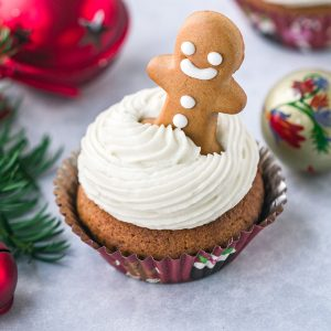 A gingerbread cupcake with a gingerbread man added into the cream cheese frosting.