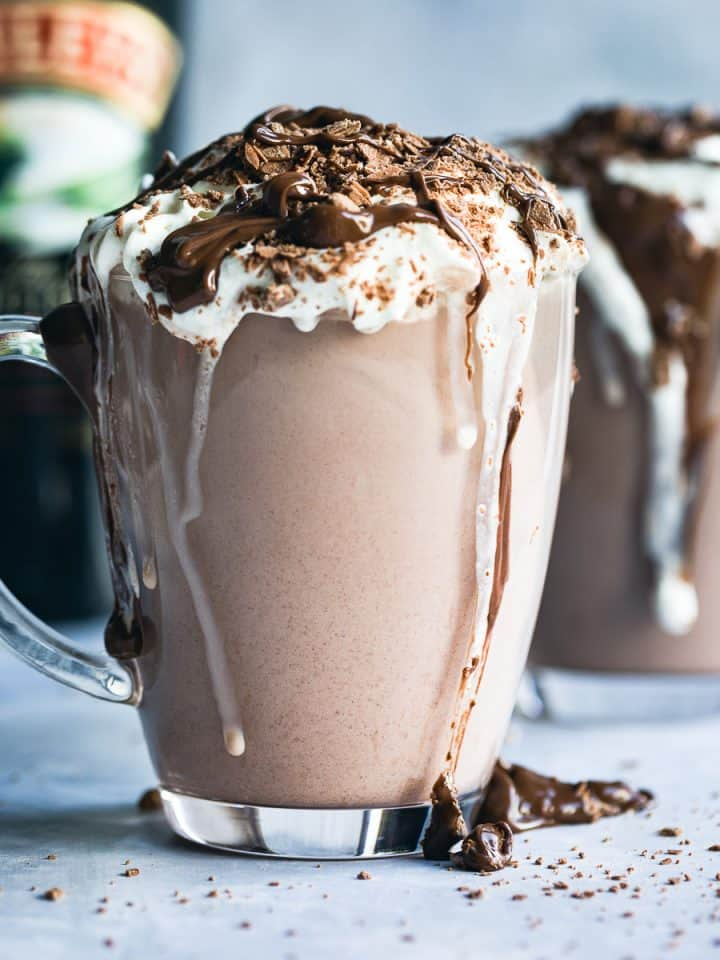 Baileys Hot Chocolate in a glass mug with cream on top, a flake crumbled over and chocolate sauce.