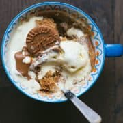 A mug filled with a microwave cake, covered with brown coloured Biscoff spread and a biscuit poking out of the top.