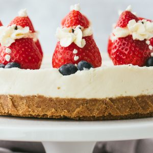 A white chocolate cheesecake with cream stuffed strawberry santas.