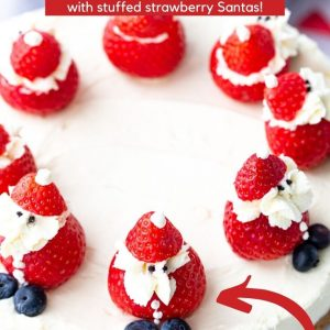 Three quarter angle image of a white coloured cheesecake with a biscuit base. There are strawberries on top that have been made to look like Santa. This is a Pinterest image with a text overlay.