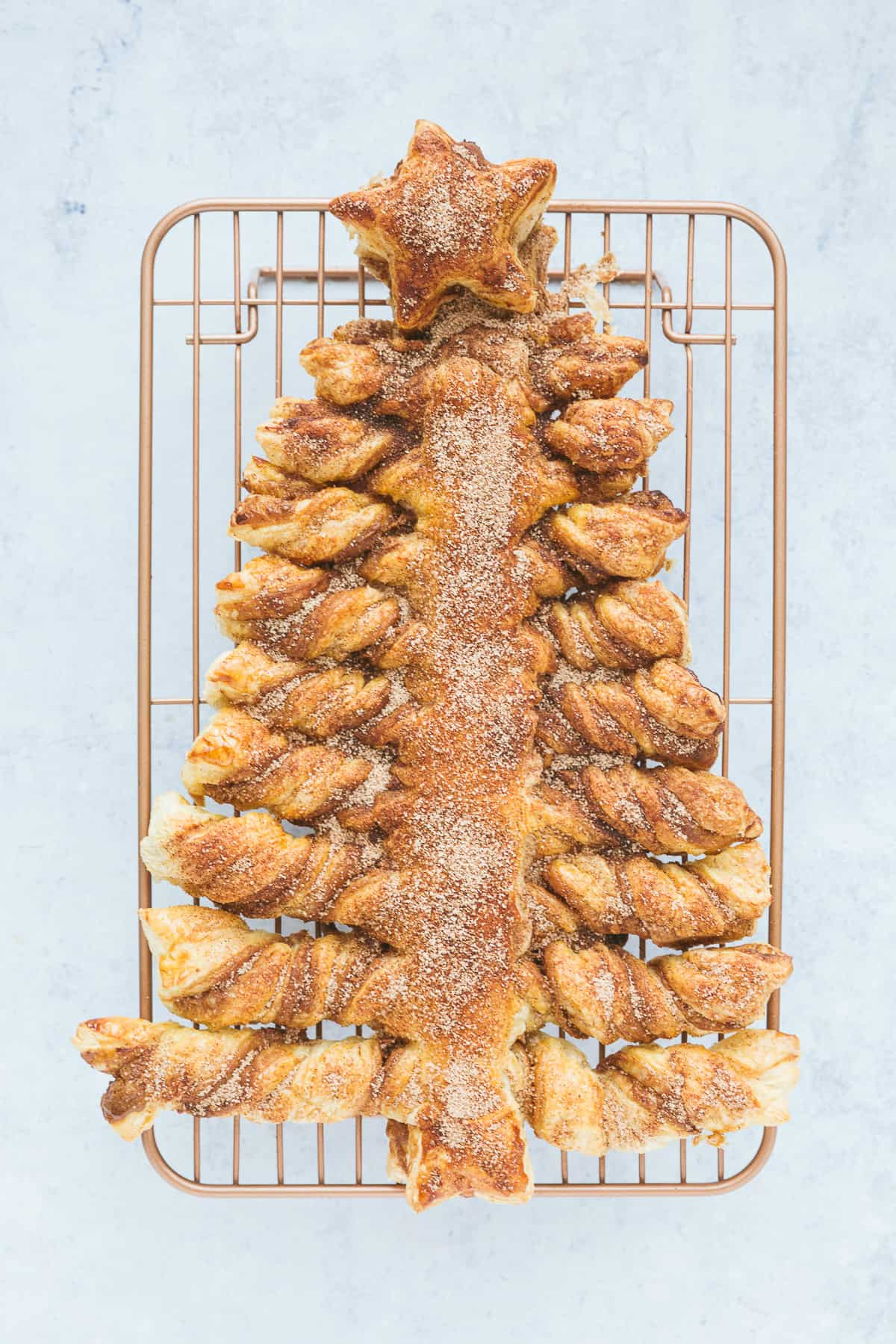 A festive Christmas tree made from ready rolled puff pastry that has been twisted into a christmas tree shape. The pastry has been filled with Biscoff spread and topped with cinnamon sugar.