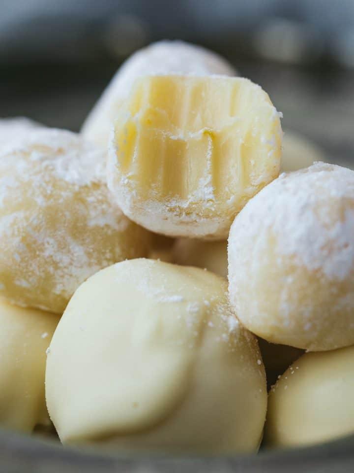 A pile of lemon truffles - one has a bite taken out of it.