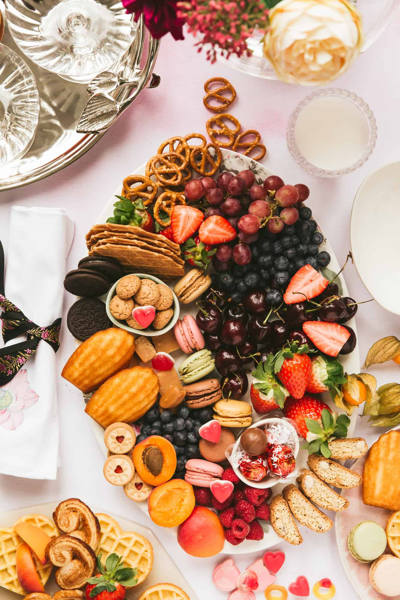 An oval platter covered with fruit and biscuits.
