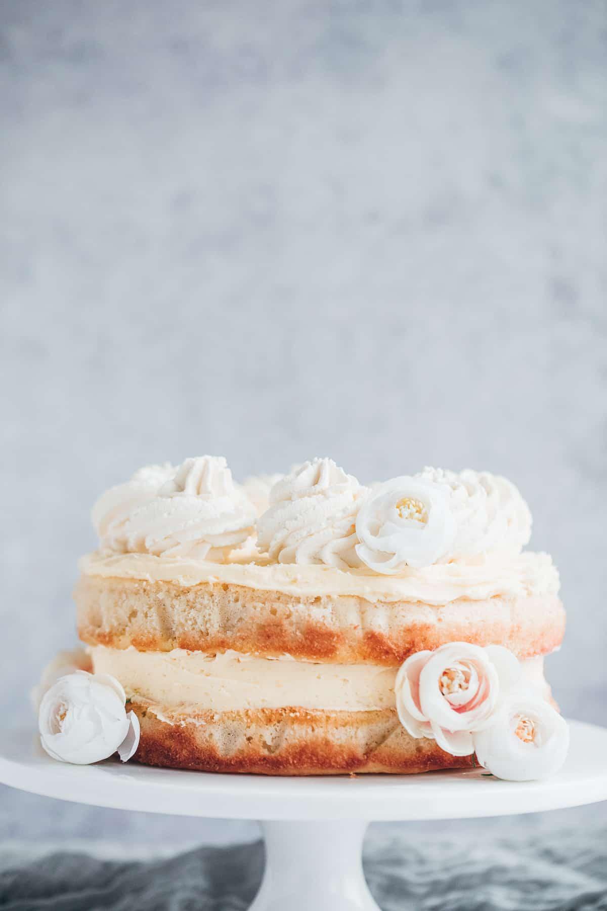 A lemon cake decorated with fresh cream swirls.
