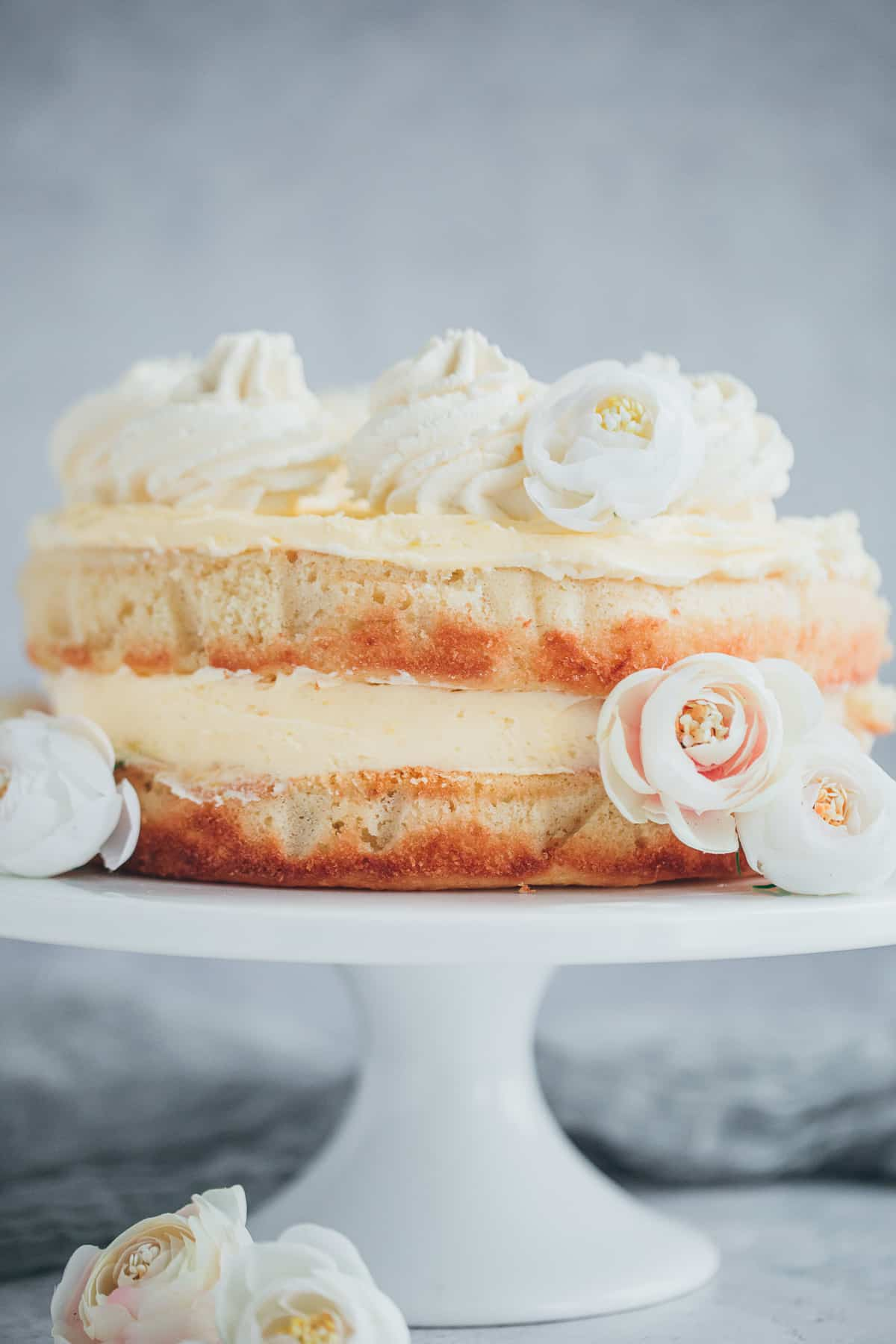 A lemon cake with a layer of lemon buttercream in the middle and a layer on top.