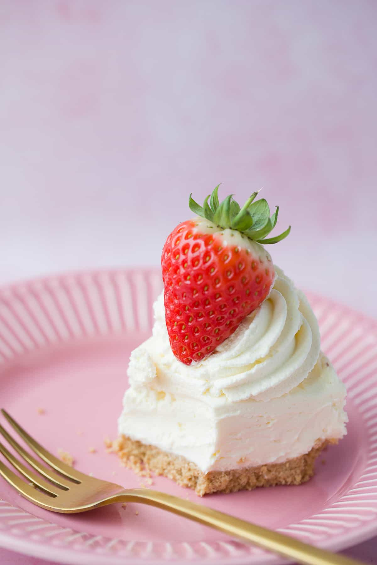 A single slice of vanilla cheesecake that has been half-eaten on a pink plate.