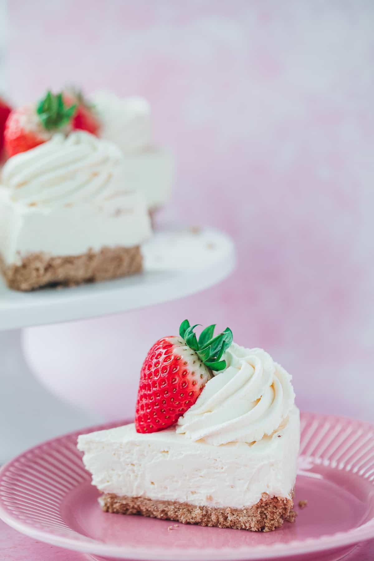 A slice of cheesecake with a cream swirl and strawberry for decoration.