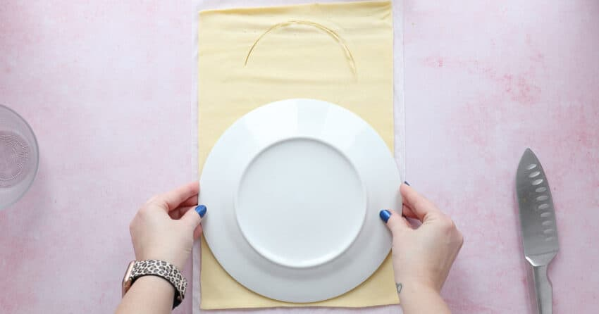 A sheet of shortcrust pastry with a plate being used as a template.