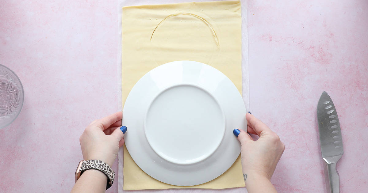 A sheet of ready rolled shortcrust pastry with a plate at the bottom being used as a template.