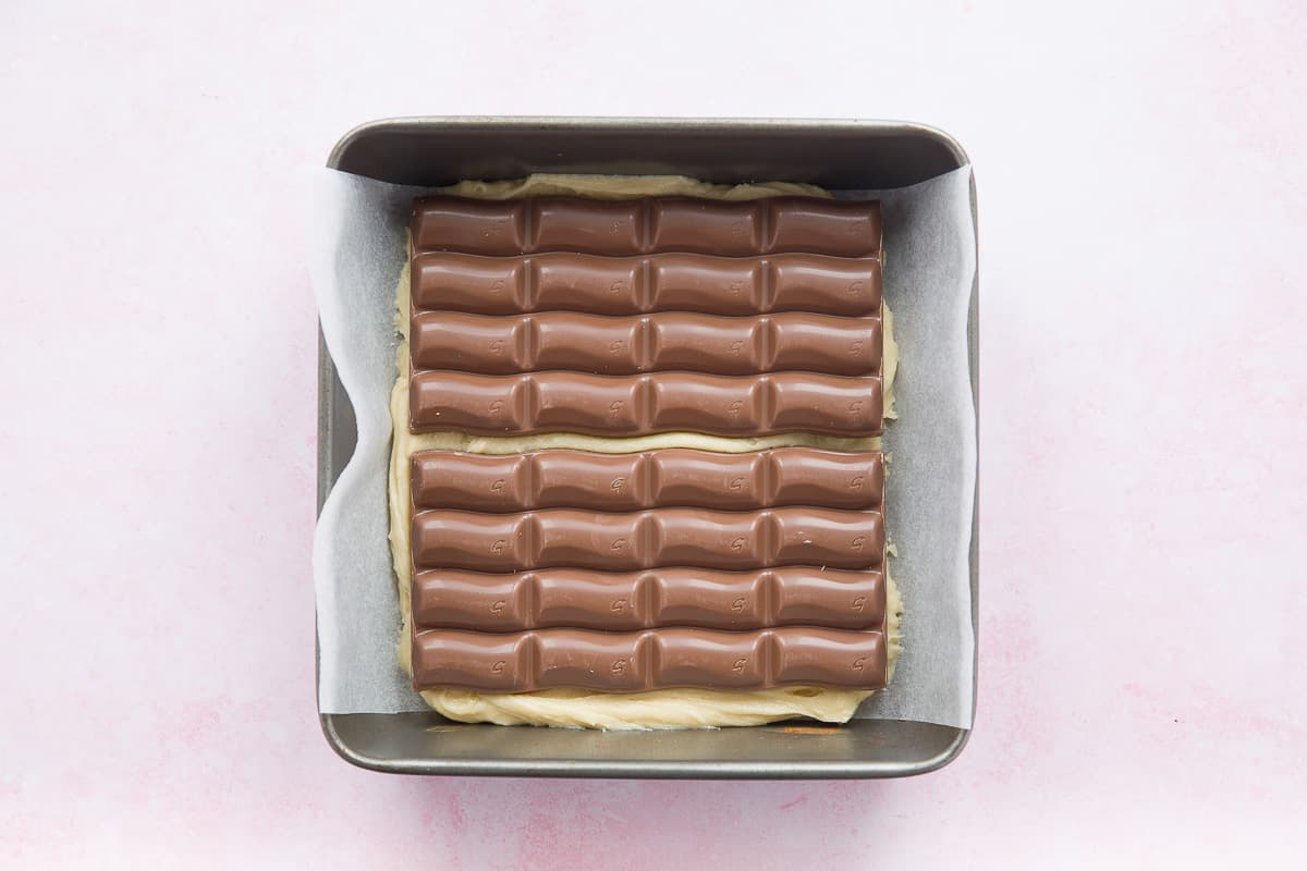 A baking tin with some mixture in. Two large chocolate bars have been added on top of the mixture.