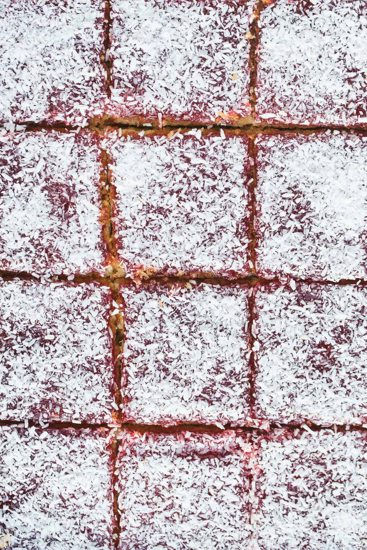 Very close up image of sponge cake with a desiccated coconut topping.