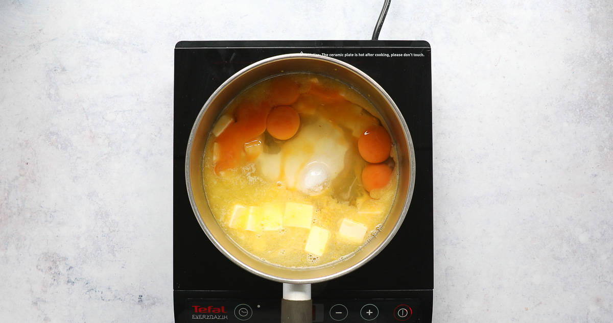 A saucepan containing the ingredients for lemon curd.