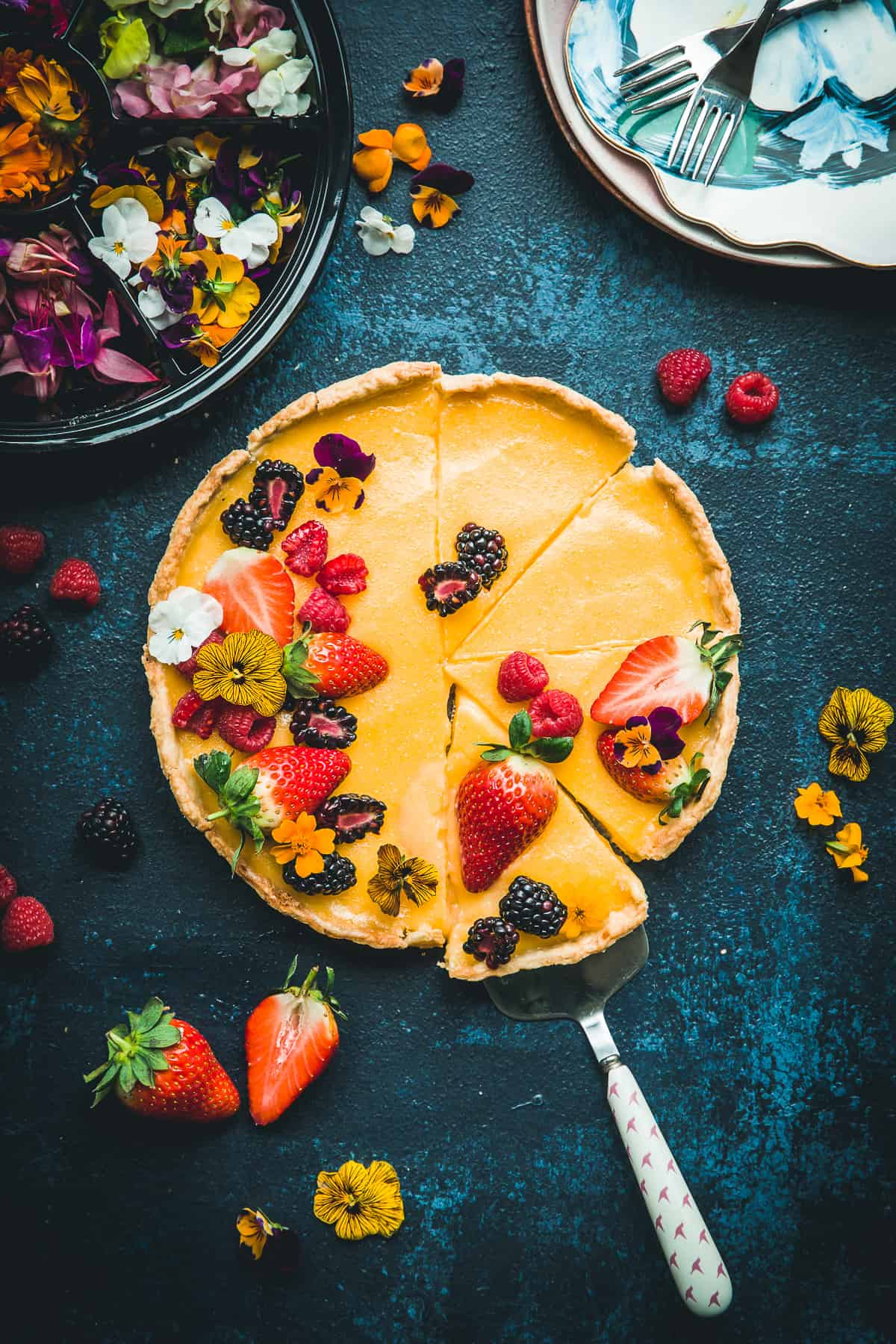A lemon pie covered with fresh berries and edible flowers.