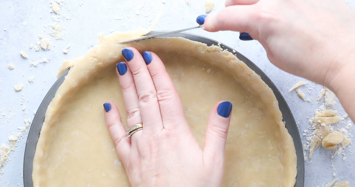 Trimming the edges of shortcrust pastry.