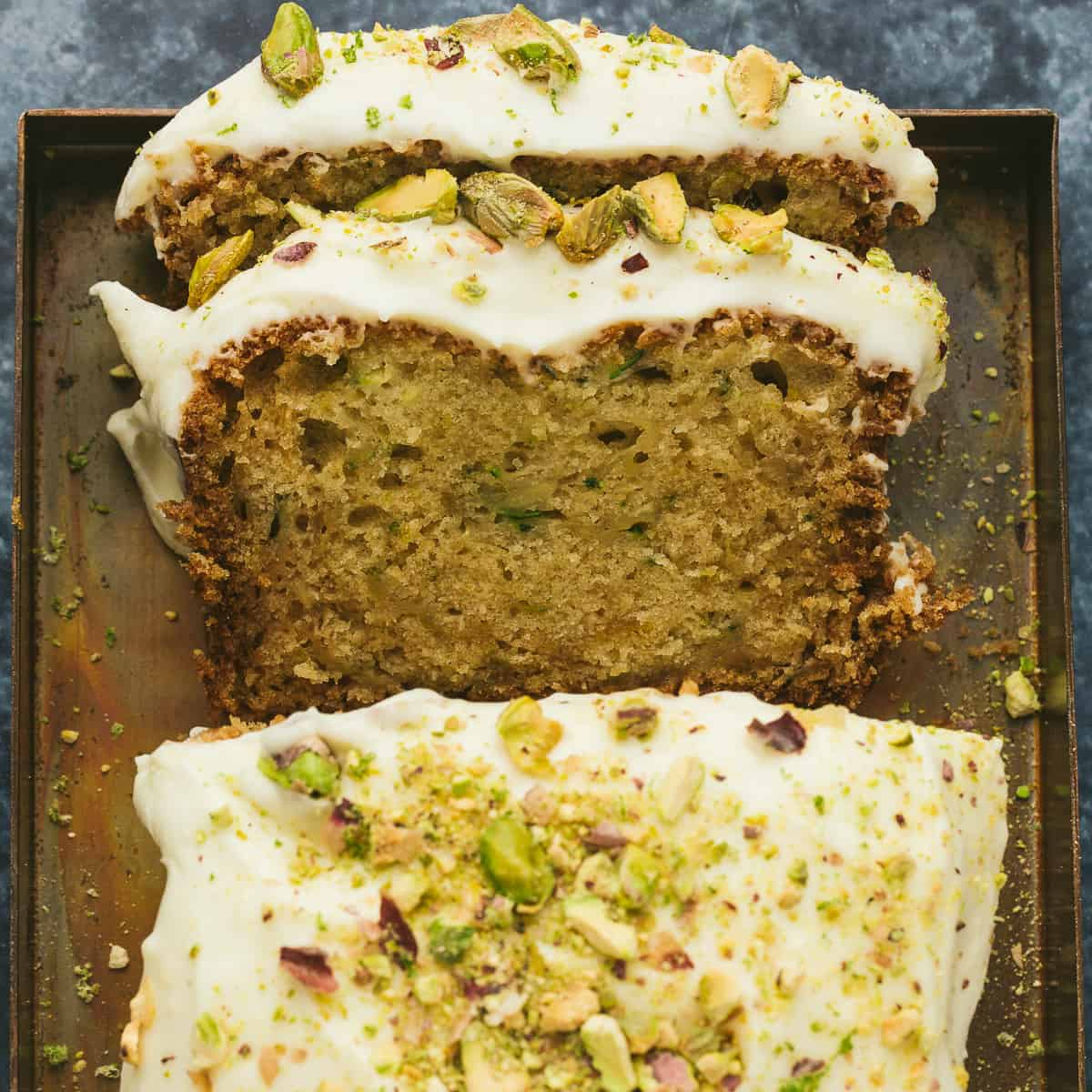 A courgette cake with two slices cut out of it.
