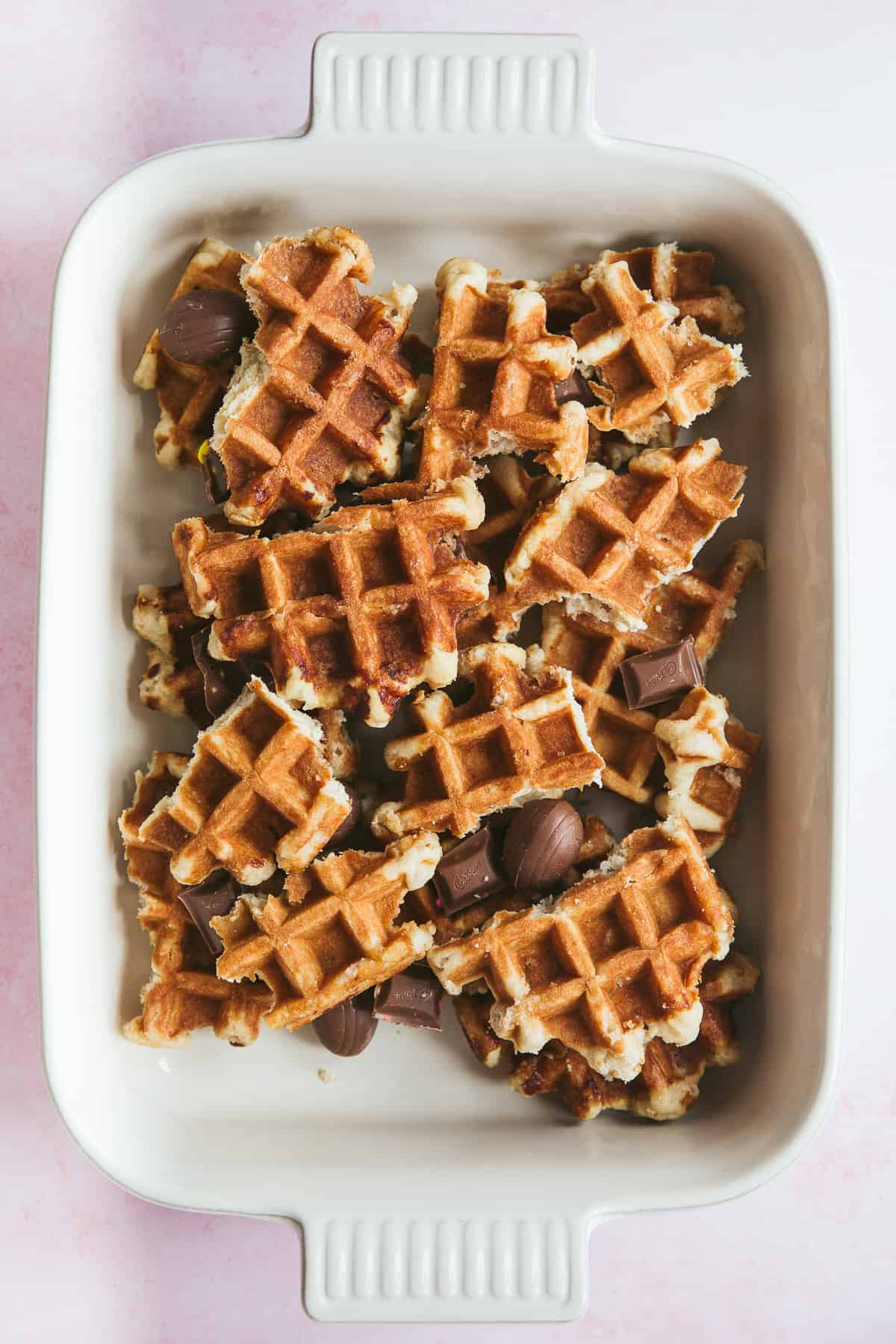 A casserole dish containing layers of broken up pieces of waffle and Easter chocolate.