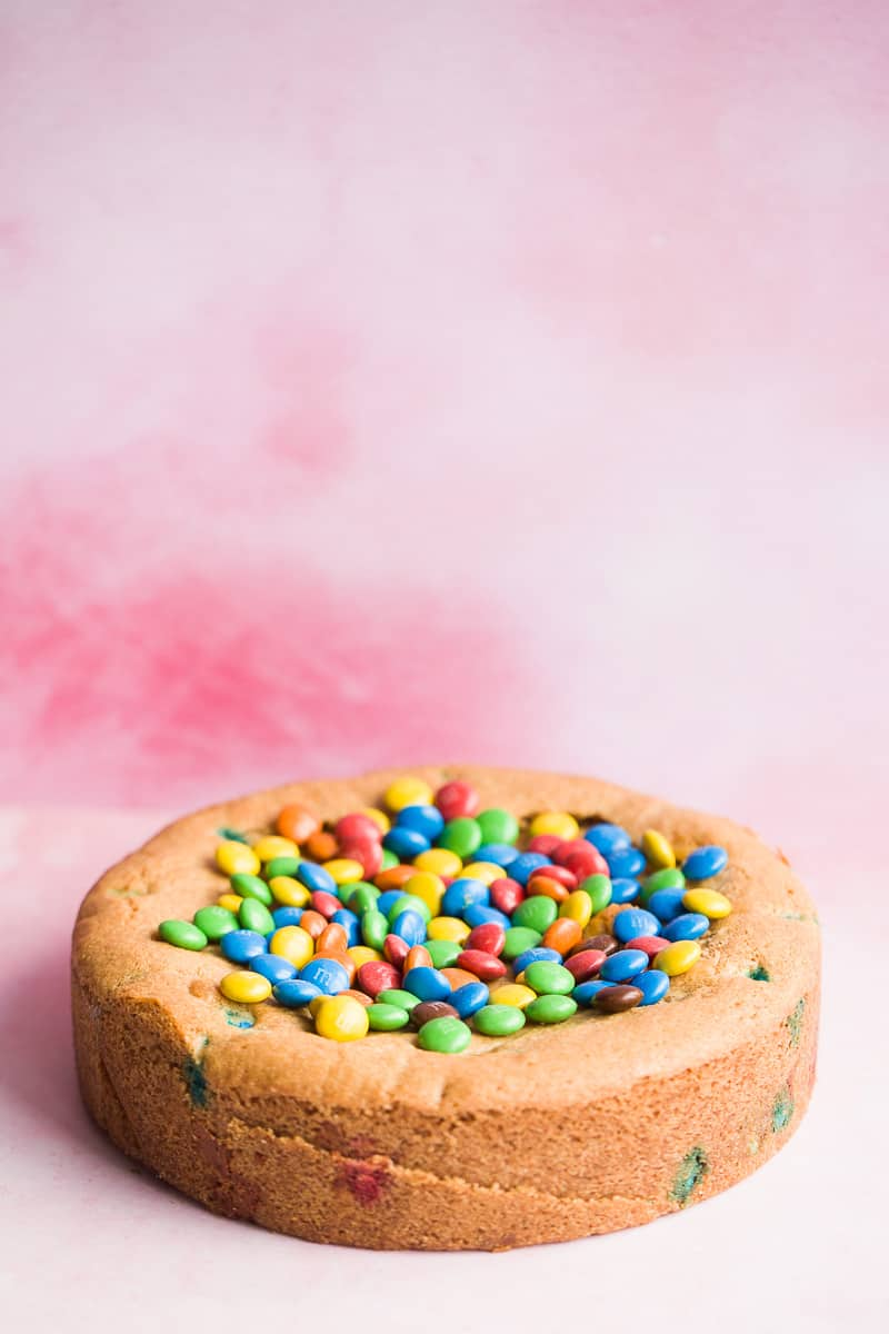 A deep dish cookie pie with colourful chocolate on top.