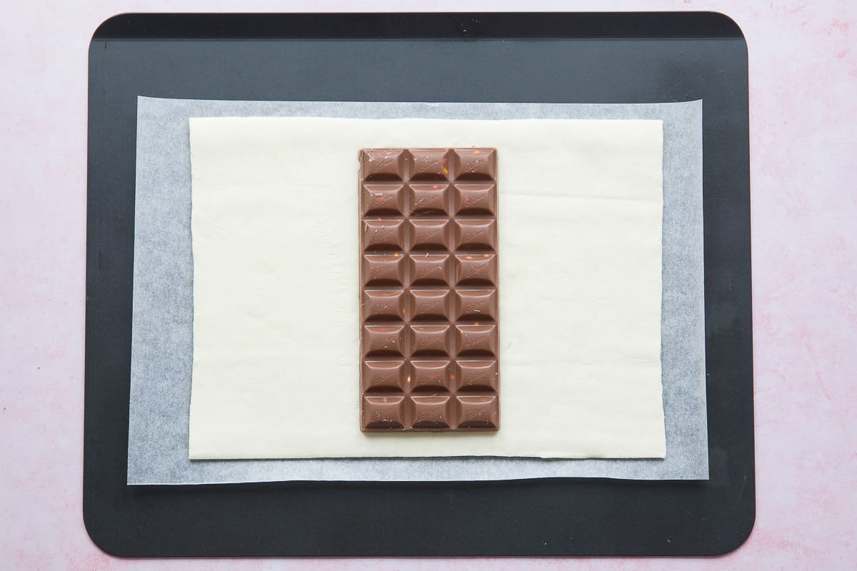 A sheet of ready rolled puff pastry with a bar of Cadbury mini egg chocolate on top.