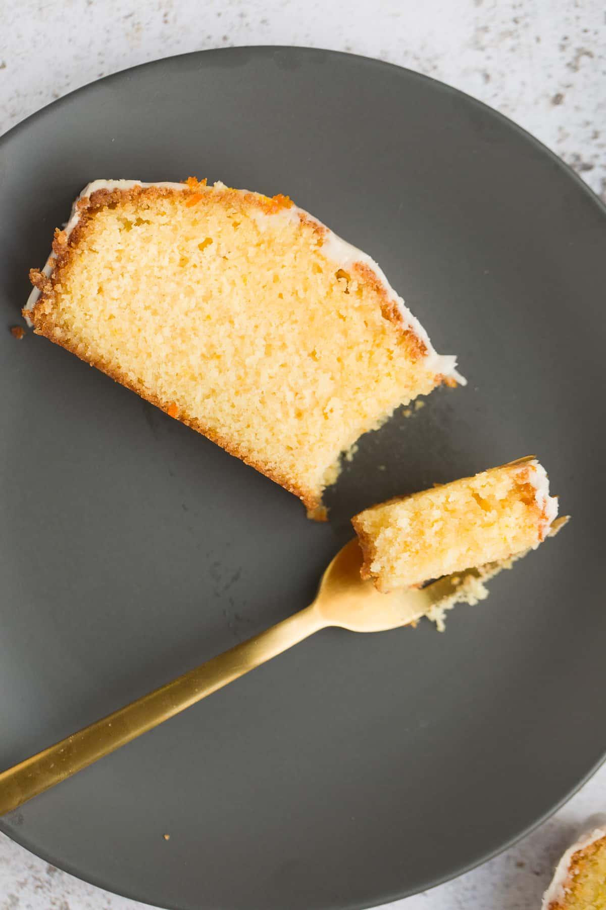 A slice of moist sponge cake on a small grey plate.