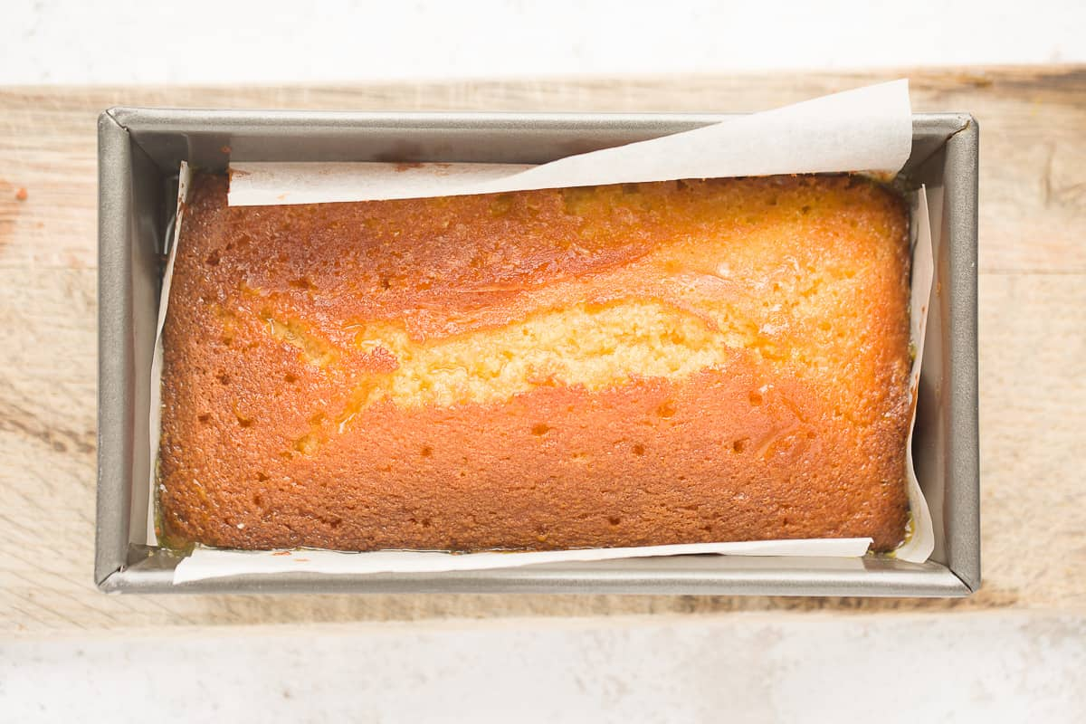 A baked orange cake that has had sugar syrup poured over the top of it. The cake looks super moist as a result.