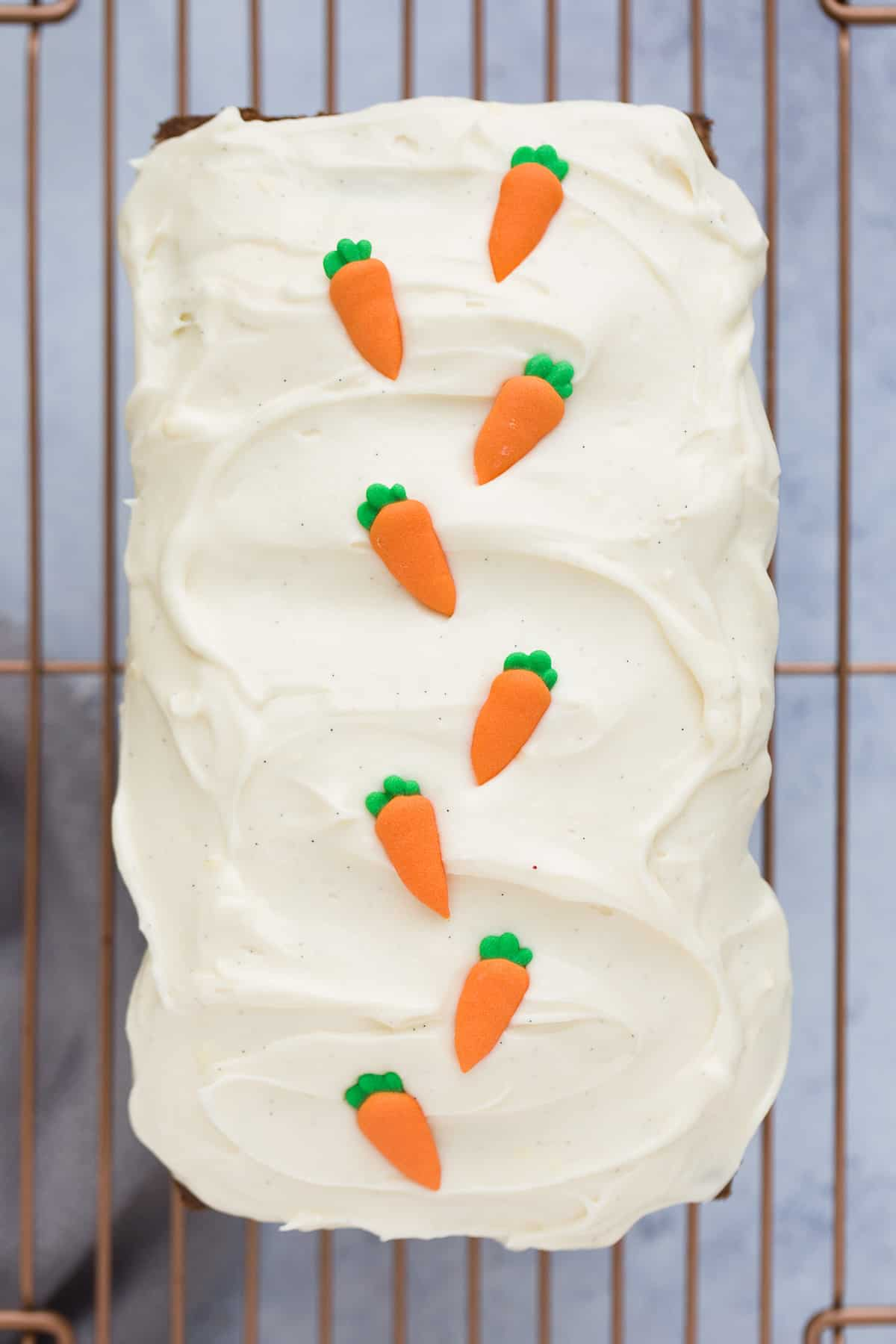 A loaf cake covered with a cream cheese frosting and 8 fondant carrots on a gold coloured wire rack.