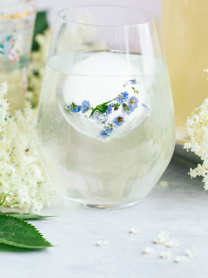 A glass of Elderflower cordial surrounded by flowers.