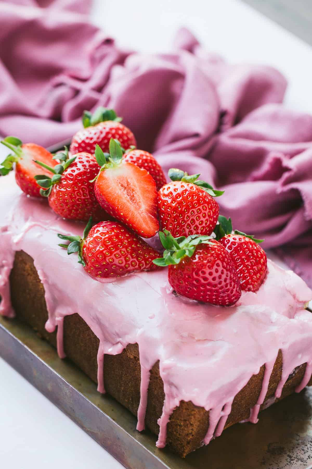 A strawberry bread with a pink coloured glaze.