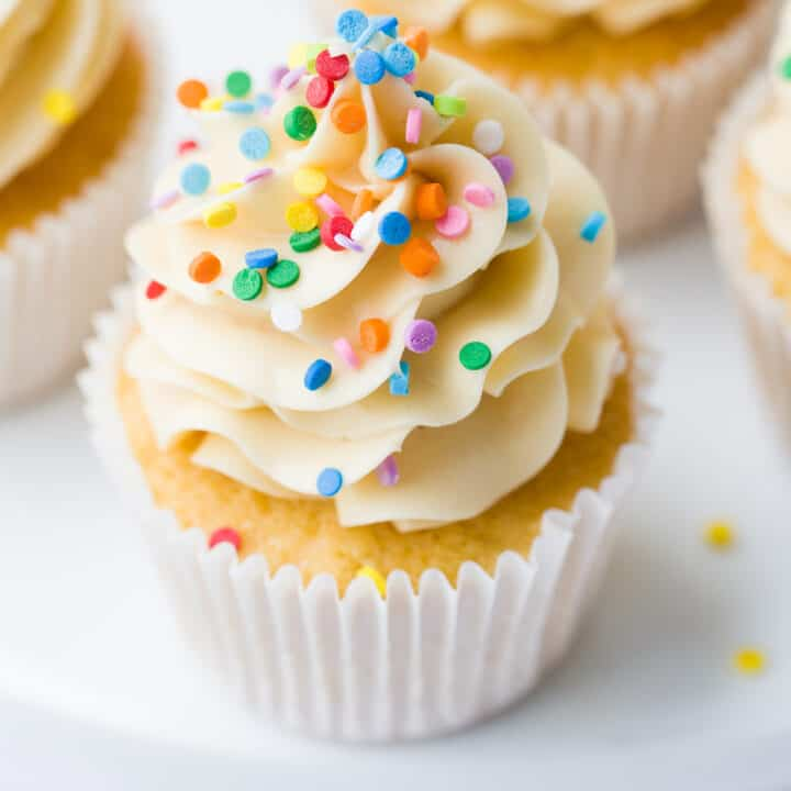 A vanilla cupcake with sprinkles on top.