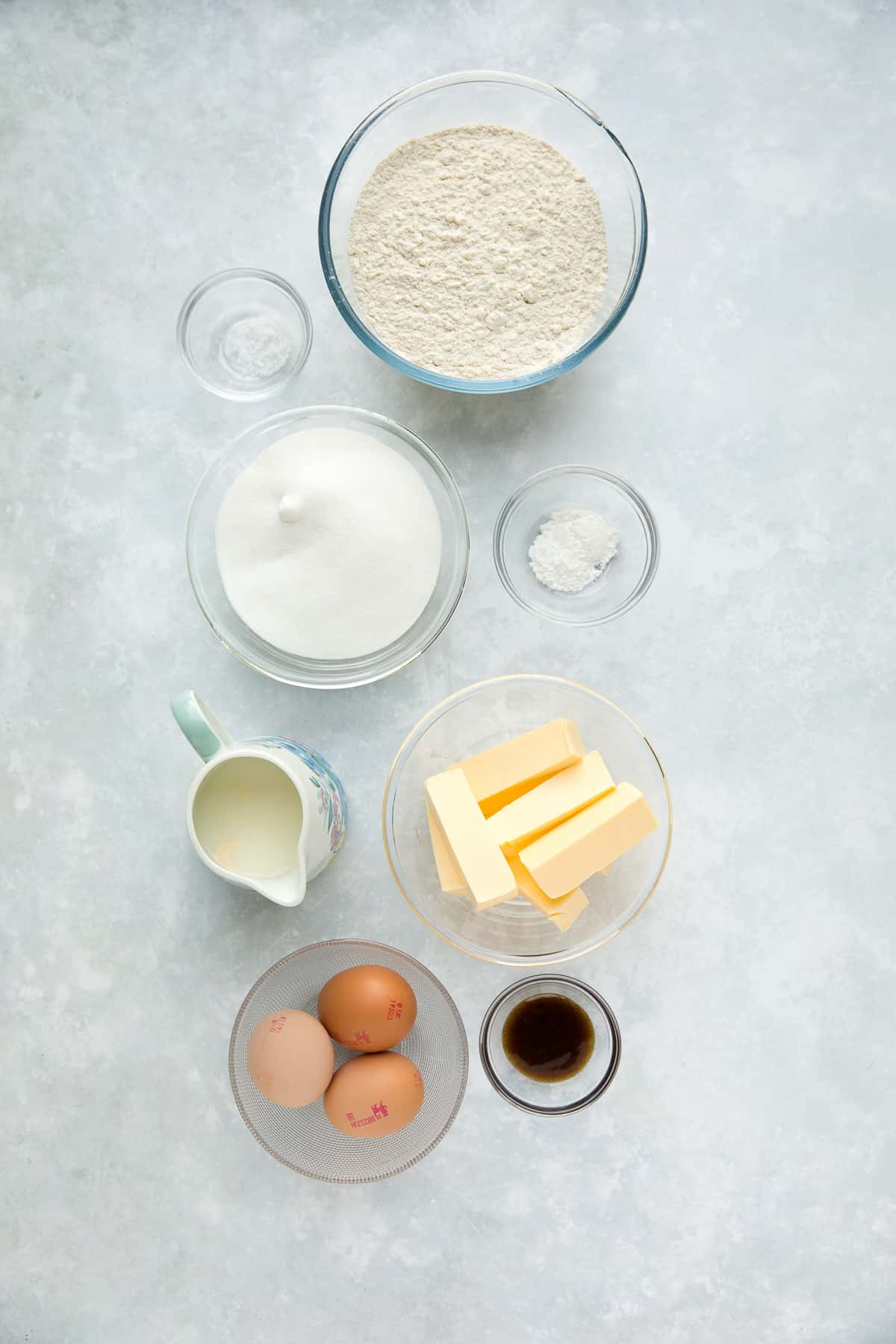 The ingredients needed for a Vanilla Loaf Cake set out in bowls.