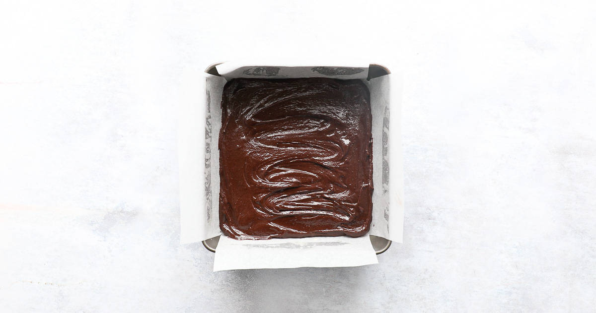 A square baking tin containing a layer of brownie mixture.