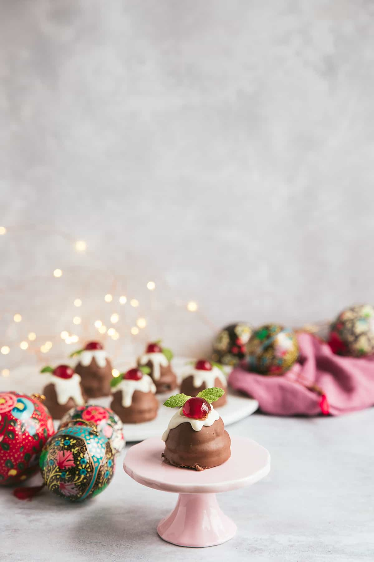 Mini vegan Christmas Puddings in a festive scene.