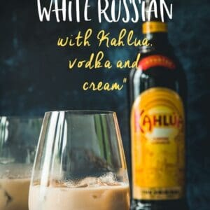 A white russian cocktail with a bottle of Kahlua in the background. Pinterest image with text overlay.